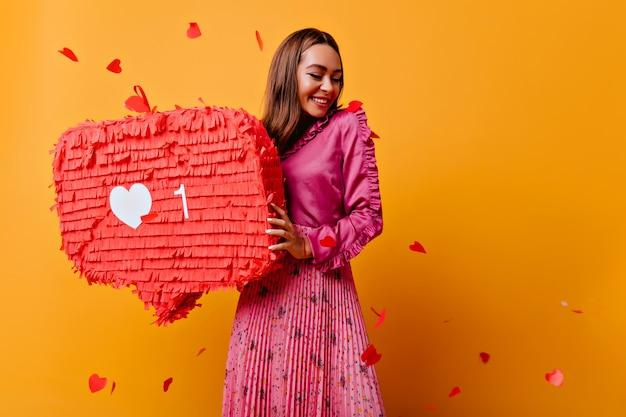 Жизнерадостная девушка с красивой улыбкой позирует с красным баннером. изысканная брюнетка женщина-блогер в хорошем настроении.