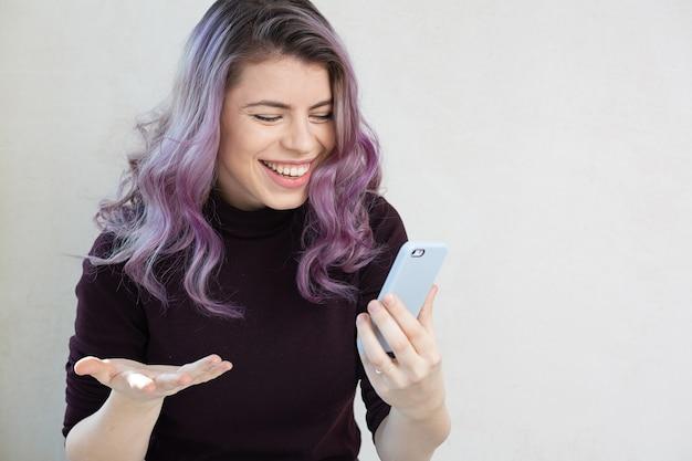 灰色の背景の上に彼女の携帯電話で見ている紫色の髪の陽気な女の子。テキスト用のスペース