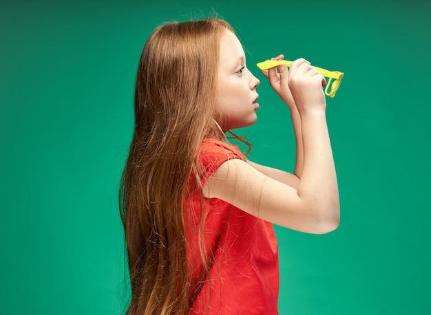 Веселая девушка с рыжими волосами и красной футболкой желтые очки эмоции студия