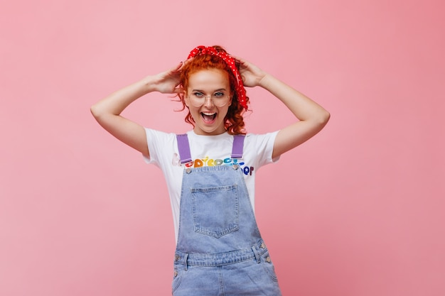Cheerful girl with red hair laughs on pink wall