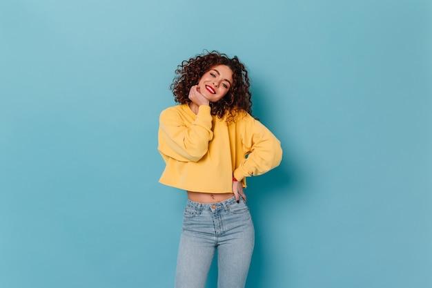 赤い唇と真っ白な笑顔の陽気な女の子が青い空間のカメラをのぞき込む。長袖とジーンズと黄色のトップでかわいい巻き毛の女性の肖像画。