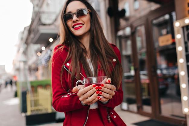 お茶のカップを保持している赤いマニキュアと陽気な女の子