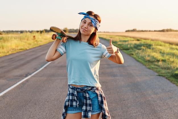 スタイリッシュなヘアバンドを持った陽気な女の子が、道を歩きながらロングボードを肩にかけ、幸せな感情でカメラを見て、親指を立ててポーズをとっています。