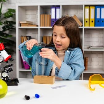 Веселая девушка с пробирками делает научные эксперименты