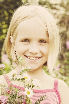 야외에서 야생 여름 꽃을 든 쾌활한 소녀