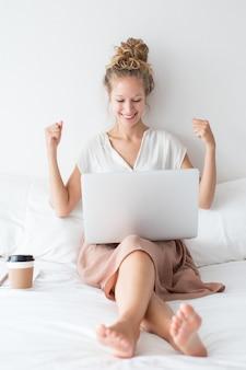 Веселая девушка, работающая на ноутбуке в постели