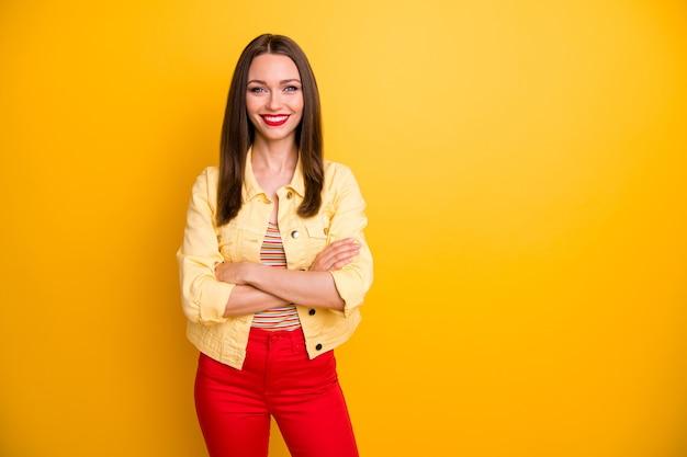 Веселая подруга в красных брюках, брюках со скрещенными руками в полосатой футболке, изолировала яркую цветную стену