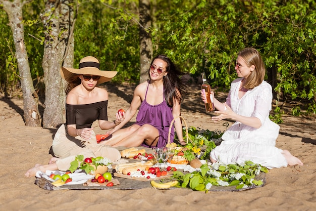Cheerful girlfriends are having fun in summer at picnic