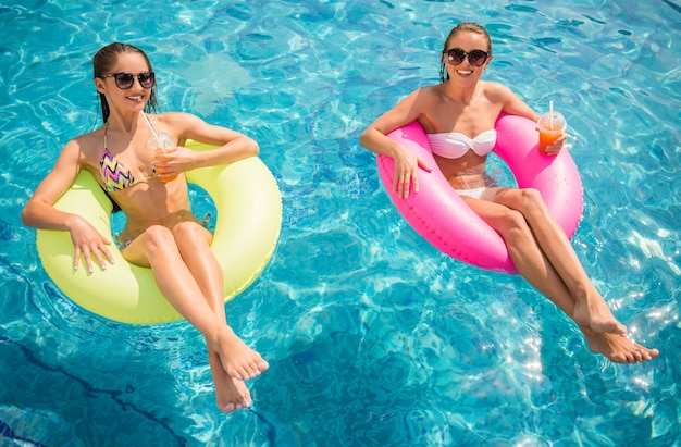 Cheerful girlfriends are having fun in swimming pool.