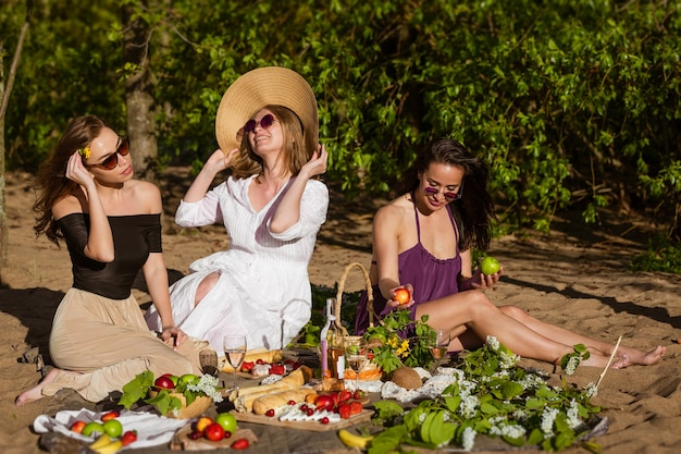 Cheerful girlfriends have fun in summer at picnic cheerful company of beautiful girls young caucasia...