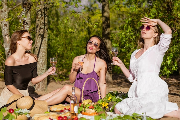 Cheerful girlfriends have fun in summer at picnic
