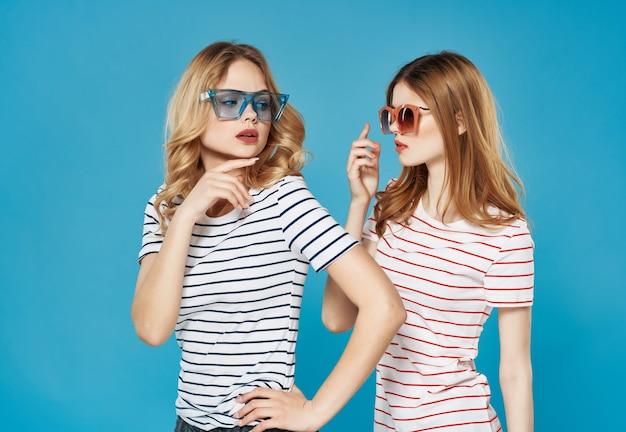 陽気なガールフレンドは、コミュニケーションの夏のスタイルの青い背景を抱きしめます