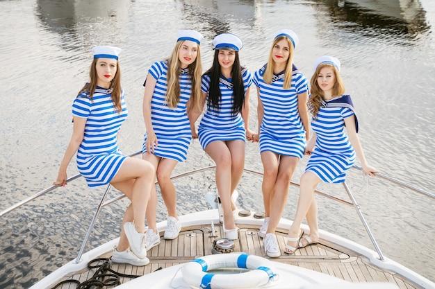 夏のヨットの縞模様のドレスとシャツの陽気なガールフレンド白人の外観の幸せな若い女性は、観光と旅行の概念を休んでいます