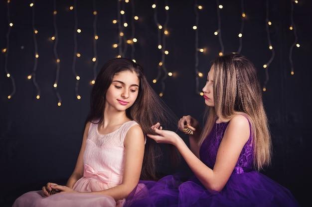 陽気なガールフレンド。二人の女の子が並んで座って、お互いの髪をとかします