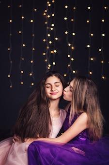 陽気なガールフレンド。ピンクと紫のドレスを着た2人の長髪の女の子