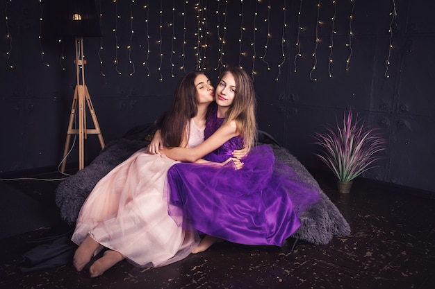 Cheerful girlfriends two long-haired girls in pink and purple dresses