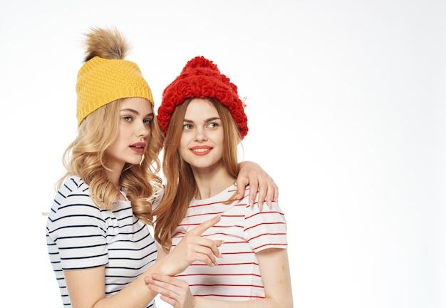 Веселые подруги в шапочках обнимаются