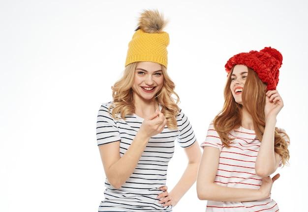 Веселые подруги в шапочках смеются