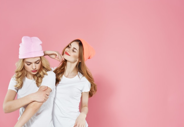 Cheerful girlfriends in white tshirts on a pink background communication friendship