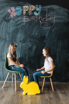 Cheerful girls on chairs near happy birthday writing