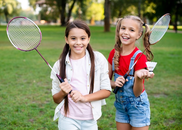 Cheerful girls holding badminton rackets in hand