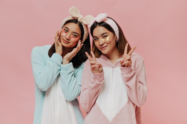 다채로운 부드러운 키구루미와 화장용 머리띠를 한 쾌활한 소녀들은 v-sign을 보여주고 아침 미용 루틴을 합니다