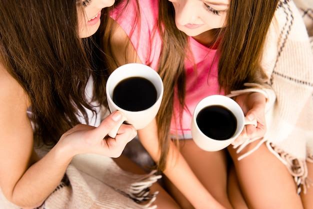Веселые девушки в пижаме с кофе