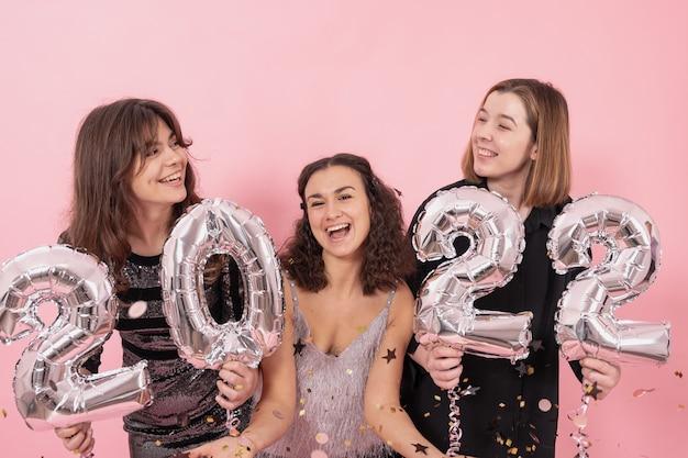 紙吹雪の中でピンクの背景に陽気な女の子は、新年の楽しみ、番号2022の銀箔の風船を持っています。