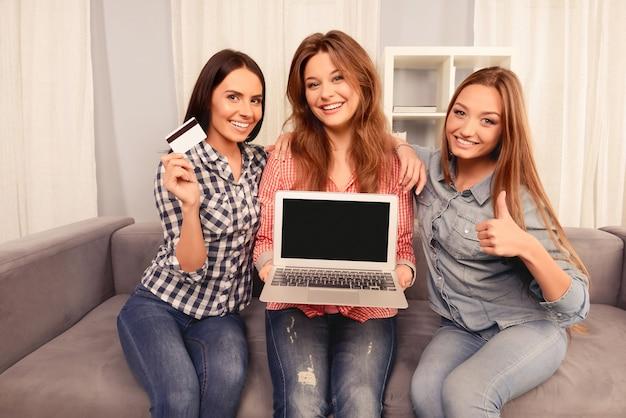 Веселые девушки показывают ноутбук, банковскую карту и показывают палец вверх