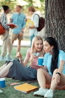 木の下に座ってコーヒーを飲み、最新ニュースについて話している陽気な女の子