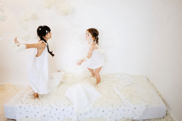 Cheerful girls throwing feathers on mattress