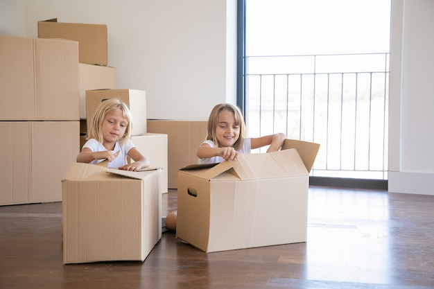 Cheerful girls unpacking things in new apartment, sitting on floor and opening cartoon boxes