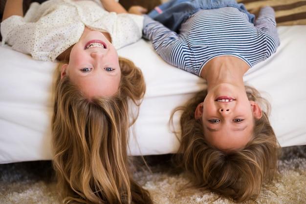 Веселые девушки вверх ногами на диване