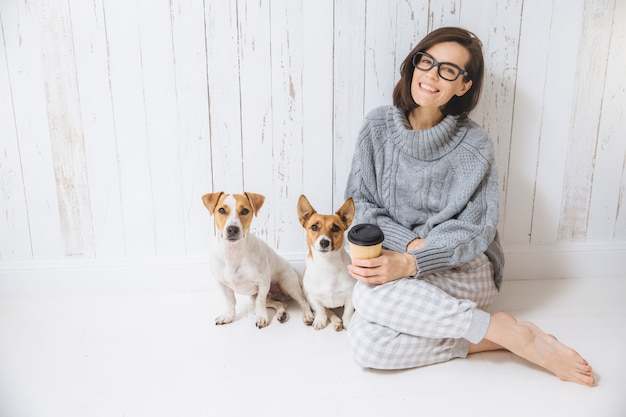 Cheerful glad brunette female dressed in warm winter knitted clothes, sits in room with her dogs