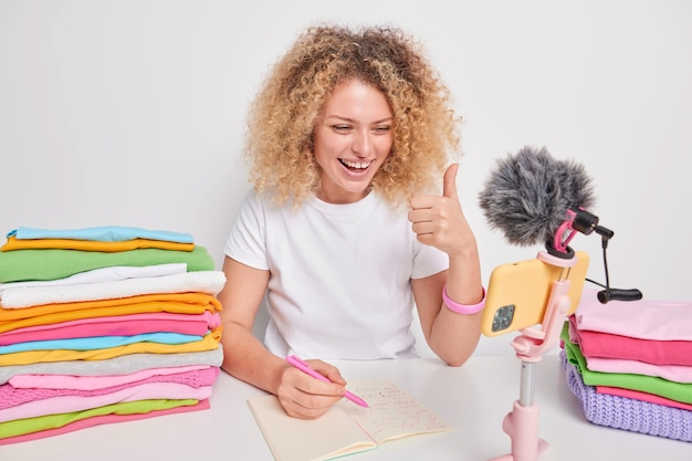 Cheerful glad curly haired woman in casual t shirt makes like gesture talks with followers has her own domestic lifestyle blog poses at table near neatly folded laundry isolated over white