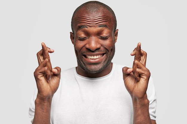 Cheerful glad dark skinned bald male hopes to win, crosses fingers, has huge desire, closes eyes with happiness, prays indoor, isolated over white wall. people and body language concept