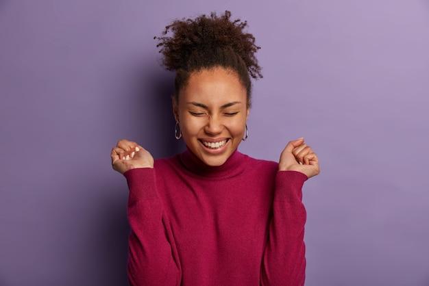 쾌활한 기쁜 민족 소녀는 주먹을 움켜 쥐고, 광범위하게 미소를 짓고, 적극적으로 몸짓을하며, 직장에서 행운이나 승진에 만족하고, 캐주얼 한 옷을 입고 보라색 벽 위에 고립되어 있습니다.