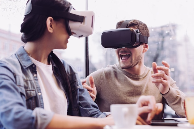 Cheerful glad gay couple wearing vr glasses while man gesturing and opening mouth