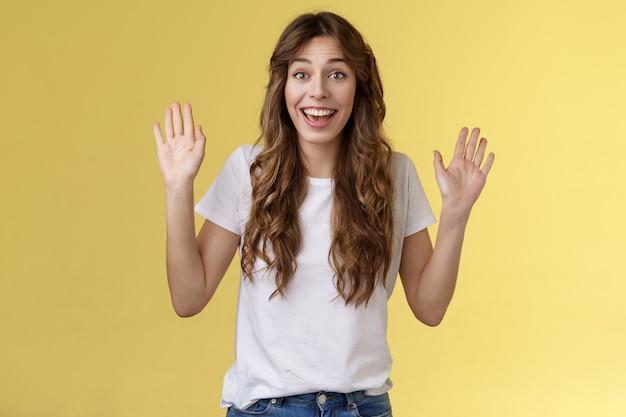 Allegra felice in uscita carina positiva giovane ragazza sorridente ampiamente alza entrambi i palmi agitando le mani ciao gesto di saluto benvenuto amico ospite sorridente ciao volentieri invito vieni dentro sfondo giallo