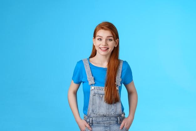 Веселая радостная рыжая женщина, стоящая в радостной расслабленной позе, одетая в джинсовый комбинезон поверх футболки, летняя одежда, довольная улыбка, беззаботная дружеская беседа, позы на синем фоне