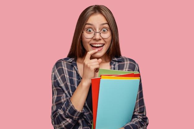 陽気な嬉しい学生は広く笑顔で、人差し指を唇の近くに保ちます