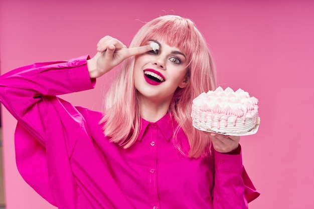 Cheerful glamorous woman holding a cake pink background sweets