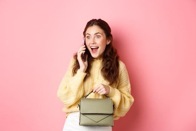 Веселая гламурная девушка выглядит удивленной во время разговора по телефону, получает удивительные новости во время звонка, держит сумочку, стоит у розовой стены
