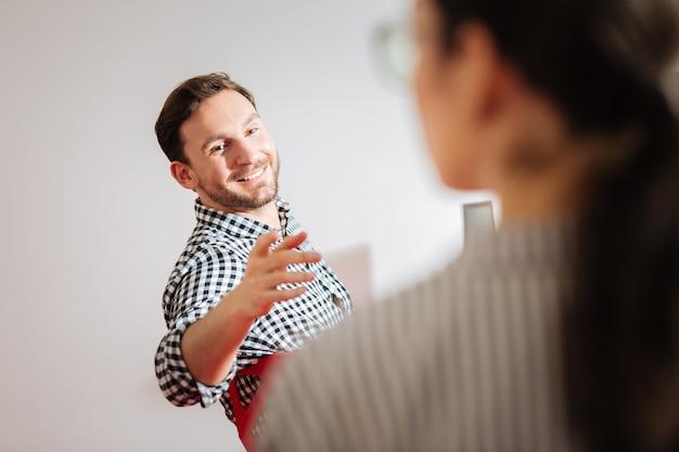 쾌활한 눈. 워크샵 중에 동료에게 연설하면서 기쁘고 웃고있는 긍정적 인 쾌활한 남자
