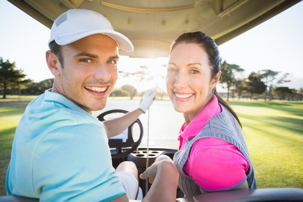 Two mature couples standing side by side on golf course