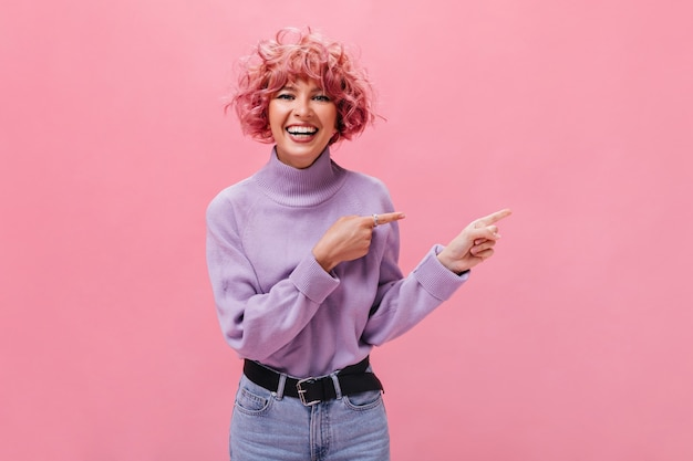 보라색 스웨터를 입은 쾌활한 유머러스한 여성이 웃고 있고 외진 곳에 있는 텍스트 위치를 가리키고 있습니다. 무료 사진