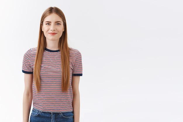 Веселая, симпатичная, уверенная в себе европейка в полосатой футболке с длинными светлыми волосами, держится за руки, ведет себя послушно и готова, уверенная в себе, может взяться за любую задачу, стоя на белом фоне позитивно