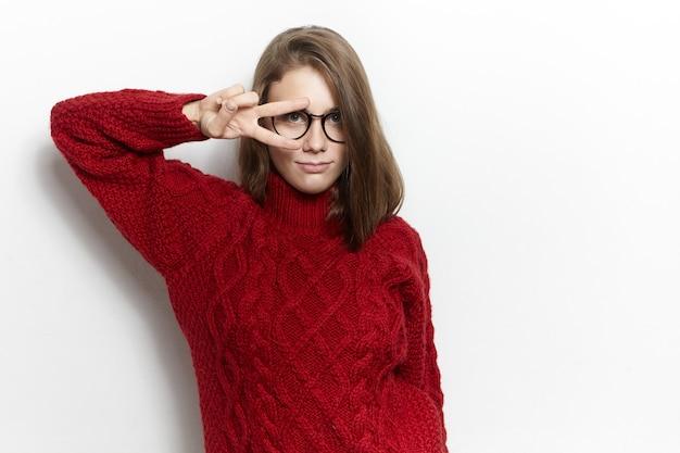 Веселая симпатичная молодая женщина в очках и вязаном свитере с высоким воротом делает знак v двумя пальцами над одним жестом глаза