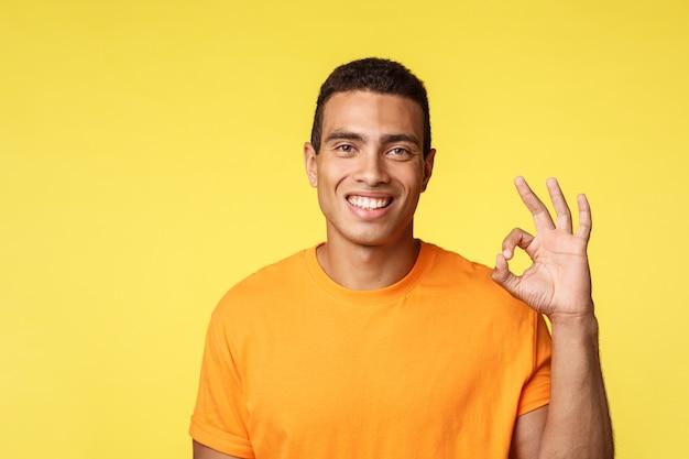 Cheerful good-looking man in t-shirt showing okay gesture
