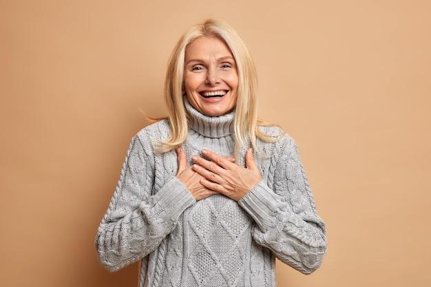 Allegra bella donna di mezza età tiene le mani premute sul petto sorride ampiamente ed esprime emozioni positive vestita in maglione invernale felice di sentire complimenti.